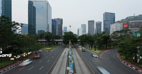 Time lapse of traffic rushing through Jakarta business district on Sudirman avenue near the Semanggi intersection in Indonesia capital city. Shot as a day to night time lapse.