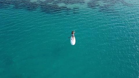 Aerial view of young girl stand up paddling on vacation. Tracking shot of a young woman SUP boarding