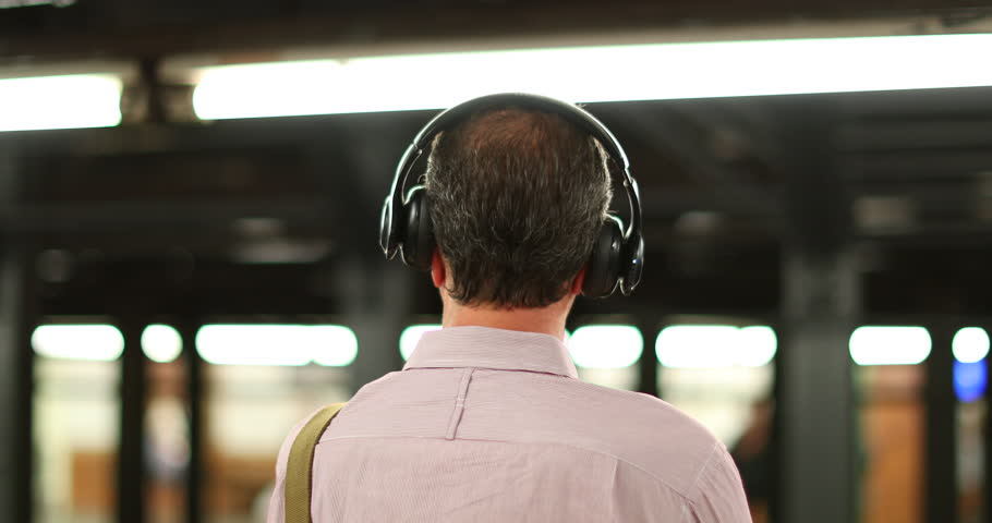 Behind back shot of man listening to music with over the ear headphones in 4K. Person listening wearing headp3hones waiting for subway metro to arrive | Shutterstock HD Video #1007235274