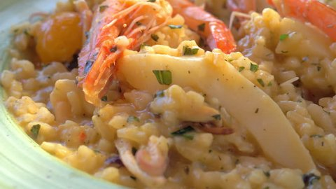 Close-up shot of dining with sea food risotto. Dish with squid and shrimps