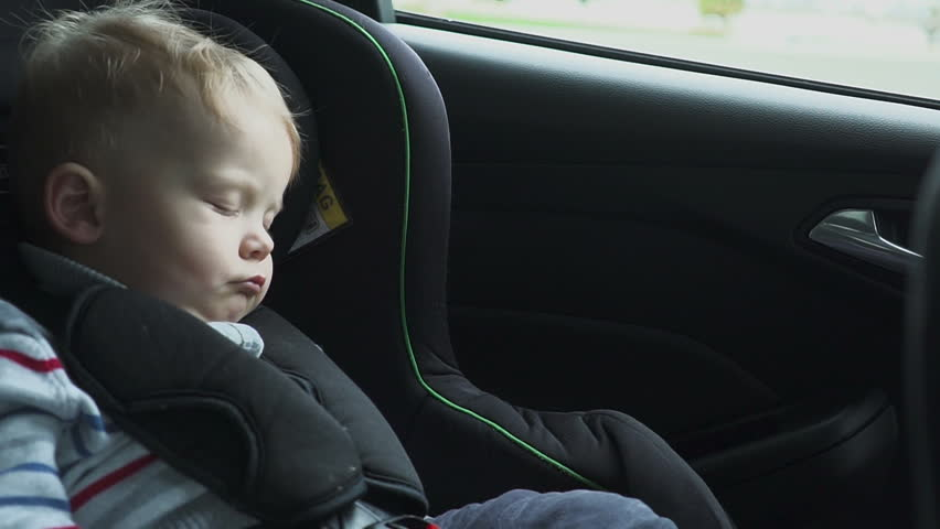 The baby sleeps in the car in the way. Sleeping child at back chair in car in slow motion. hd