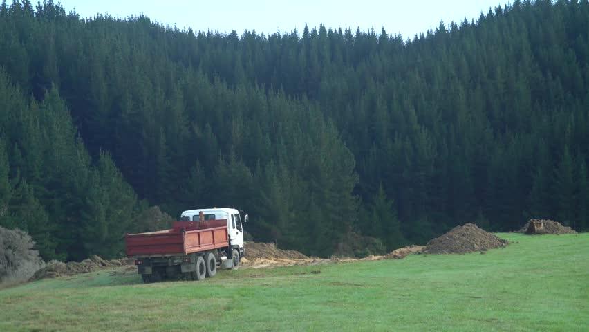 Retro pickup and dump truck near dirt mound in grassy alpine landscape in Abel Tasman, New Zealand.