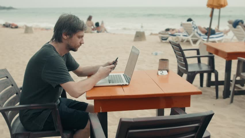 Man with laptop and mobile phone running remotely on colorful beach of island, among the palms cafe. Hotel view sea ocean | Shutterstock HD Video #1007276194