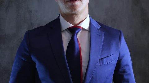 stylish man correcting cravat on neck on background of gray concrete wall, close-up