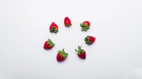 Stop motion. Strawberries appear one by one and dancing, top view
