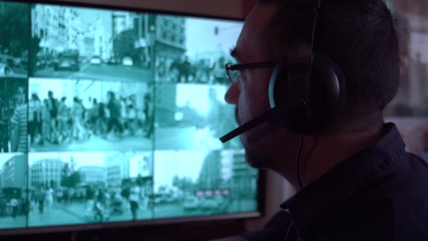Security officer watching monitoring displays in control room. Security cameras. Security surveillance system monitor. Security worker in control room taking calls via headsets | Shutterstock HD Video #1007313154