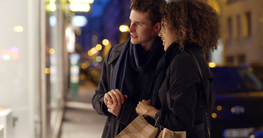 Attractive young couple window shopping in Paris. Caucasian male and African female admire window display in evening. 4k | Shutterstock HD Video #1007326924