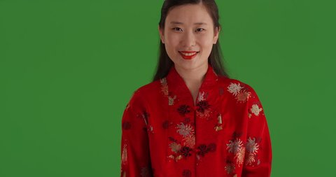 Joyful asian woman with smile wearing traditional Chinese style suit and isolated on green screen. Happy Chinese girl standing in front green chroma key wearing traditional asian fashion. 4k