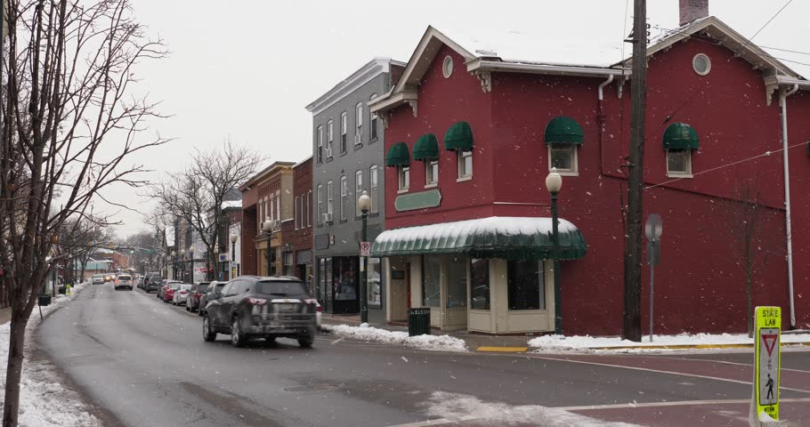 A daytime winter exterior establishing shot of a generic small town's Main Street shopping district storefronts and traffic. Store marquees digitally removed for customization.