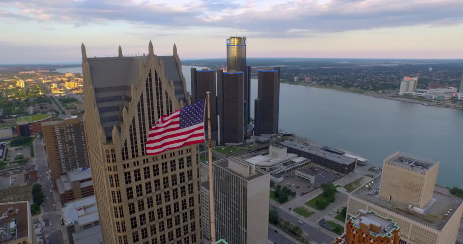 Revealing aerial pullback flying around buildings in Detroit's downtown.