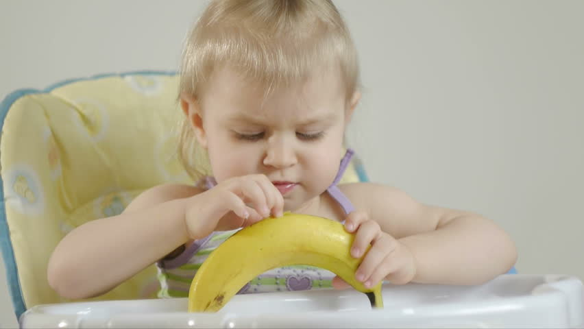 Little girl sitting in a baby chair eating a banana | Shutterstock HD Video #1007364124