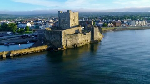 Medieval Norman Castle in Carrickfergus near Belfast in sunrise light. Aerial 4K flyby video with marina, yachts, parking, town and far view of Belfast in the background.