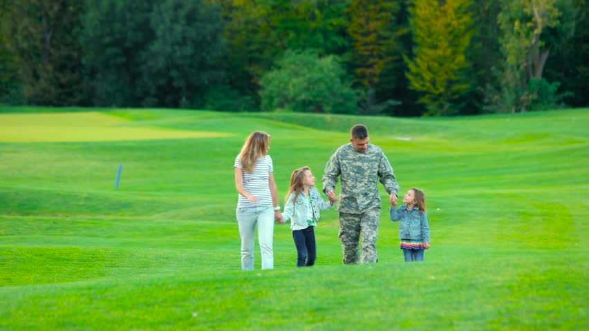 Happy soldier with his family in park. Man in camoubackgrounde, wife and two little daughters.