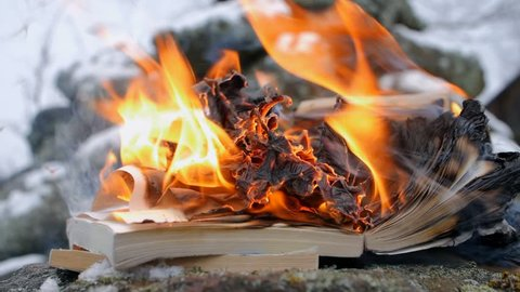 burning books on the background of stones and snow