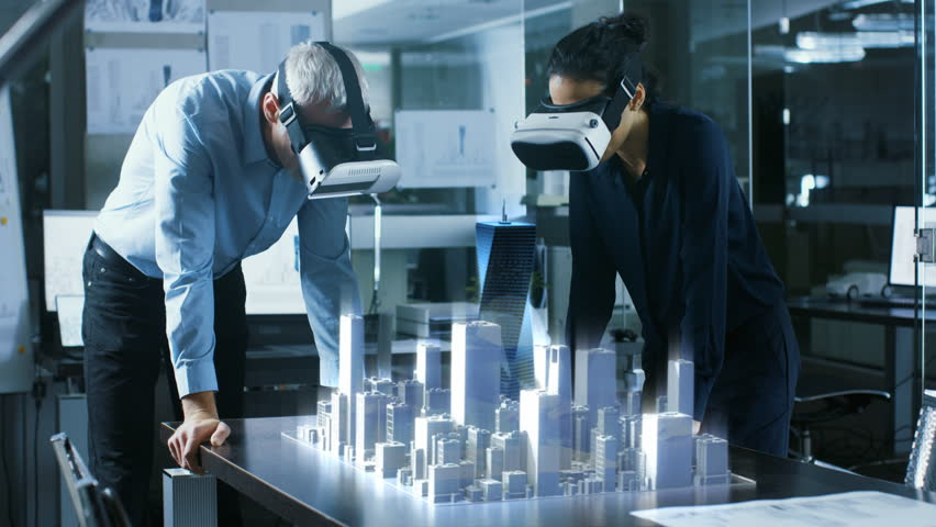 Male and Female Architects Wearing  Augmented Reality Headsets Work with 3D City Model. High Tech Office Professional People Use Virtual Reality Modeling Software Application. | Shutterstock HD Video #1007401264