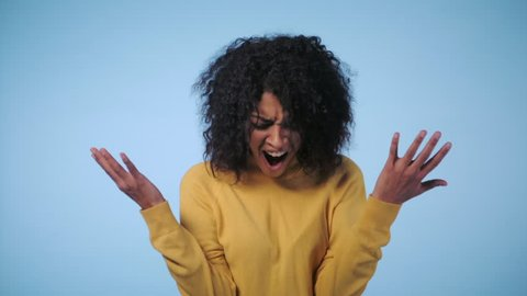 Close up of a young african american stressed afro girl shouting isolated over blue background. Slow motion. Stressed and depressed woman in yellow clothing