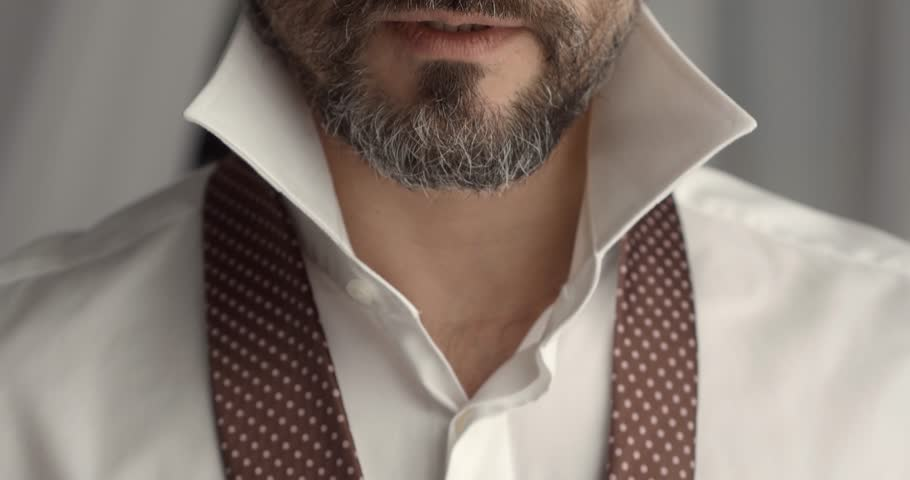man in shirt dressing up and adjusting tie on neck at home. Is going to work.