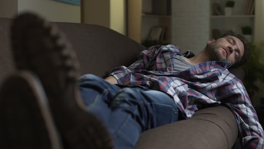 Drunken man sleeping on couch, scratching belly in his sleep, after night out
