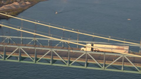AERIAL: Flying above freight container semi trucks driving across the Ambassador bridge into the transportation & warehousing logistic center in Detroit, USA. Heavy traffic on multiple lane highway