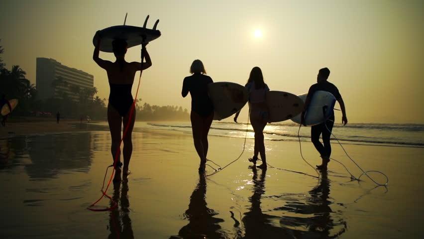 Silhouette surfers walk with surfboard beach golden sunrise rapid slow motion
