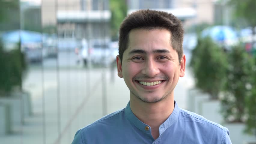 Young man asian smiling and looking at camera. Portrait of a happy handsome young man in a urban street. Close up face of young cool trendy man looking at camera | Shutterstock HD Video #1007460034