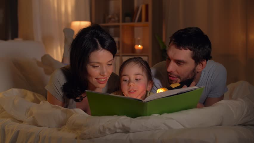 people and family concept - happy mother, father and little daughter reading book with torch light in bed at home