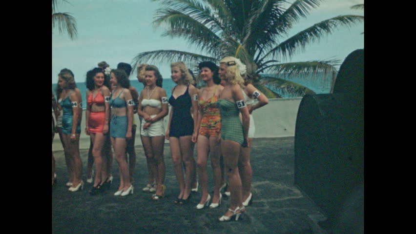 1940s: Beauty pageant, long line of women with numbered armbands stand in swimsuits in front of palm trees, pose. Women all begin to walk forward. Swimmers do the butterfly.