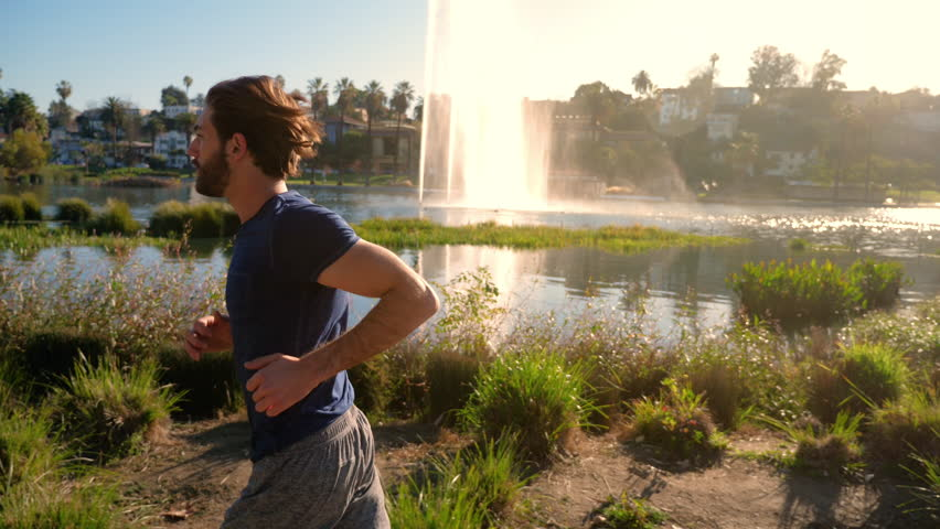 Athletic man jogs around a small lake in Los Angeles. Buildings of Los Angeles skyline can be seen in the distance. | Shutterstock HD Video #1007502292