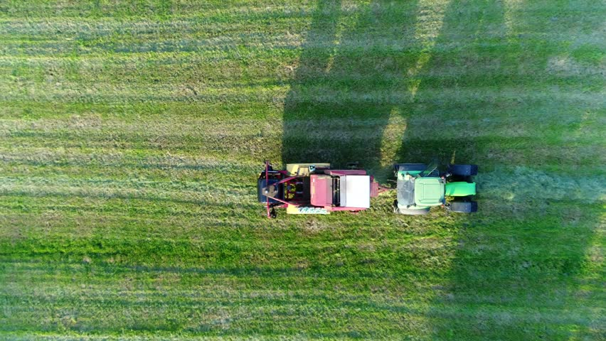 Aerial top down view of tractor pulling plastic bale wrapping machinery used for pickup of dried grass hay then wrapping it into large bale which then is storage for animal fodder used for winter feed