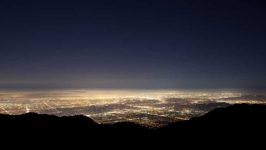 4K time lapse high angle wide shot of stars and airplanes in a clear sky above the glow of the Los Angeles Basin city lights silhouetting the San Gabriel Mountains in California as fog approaches | Shutterstock HD Video #1007511697
