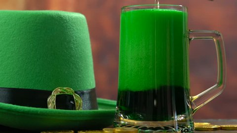 St Patrick's Day pouring green beer with green leprechaun hat and gold coins against rustic background, panning up.