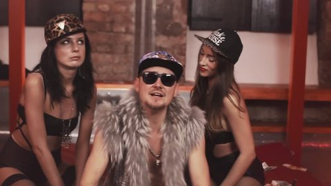 Wealthy caucasian hip hop man in fur vest with glasses and snapback with sexy girls in underwear sitting on bed covered in money rapping