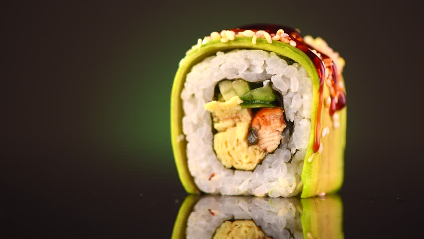 Sushi rolls japanese food rotated over black background. Sushi roll with salmon, tofu, vegetables and avocado closeup, rotation. Japan restaurant menu. 4K UHD video