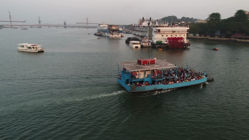Small blue ferryboat floats on Mandovi river in Panaji, Goa, india. A crowd of people on boat and on shore. Aerial view.