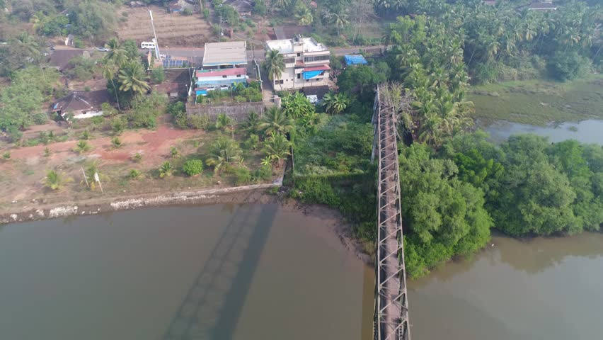Flying over a long aqueduct over a muddy river. A shadow of the structure falls on the water of the river. Shot with a drone in Goa, India. | Shutterstock HD Video #1007526019