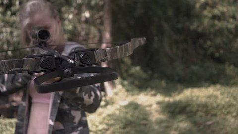 2 in 1 video. blonde in camo jacket is shooting from a crossbow camera rotating