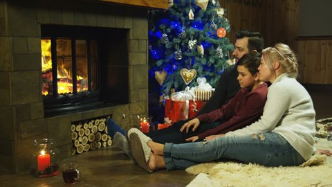 Wide view of young family relaxing on a shaggy rug in front of a burning fire and Christmas tree with burning candles as they spend time together. Shot on Red cinema camera.