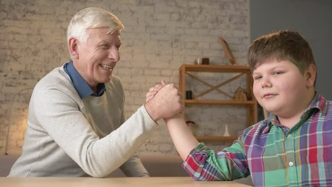 Grandfather and grandson arm wrestle in a cozy room at home. Measuring forces in arm wrestling. Old man won. Home comfort, family idyll, cosiness concept, difference of generations, close up. 60 fps