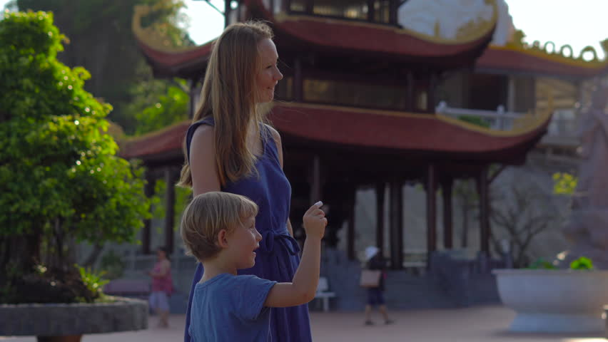 Steadycam shot of a young woman and her son visiting a budhist temple Ho Quoc Pagoda on Phu Quoc island, Vietnam