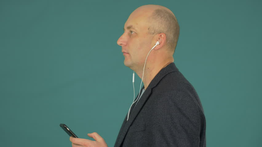 Bald middle aged businessman listening music with earphones and smartphone | Shutterstock HD Video #1007557996