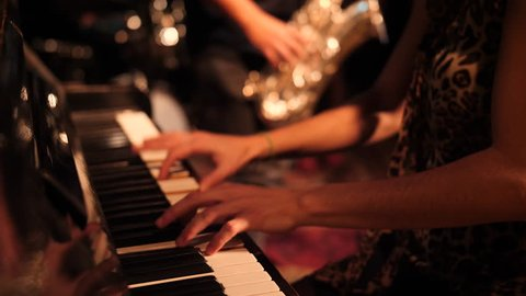 Pianist in latin band pounding keys live at night club.