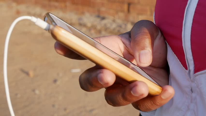 A South African black persons hand texting on her cellphone standing on a rural dirt road.   Shutterstock HD Video #1007561224