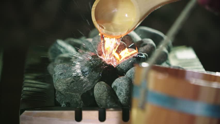 Slow motion close up shot of a wet sauna. Splash water on hot stones
