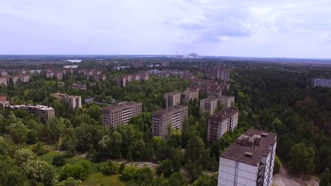 Aerial shot. Abandoned houses of Pripyat on the background of the Chernobyl nuclear power plant
