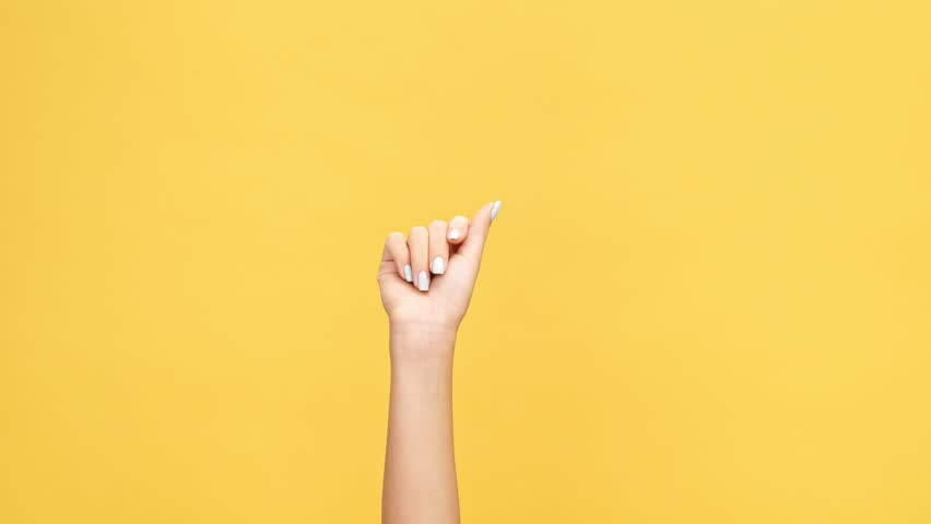 Woman hand snaps her fingers over yellow background | Shutterstock HD Video #1007574784
