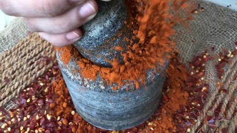 Slow motion of Indian spices hand pounding red chili flakes crushed in stone mortar, chef preparing traditional spicy hot curry India