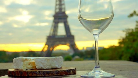 Red wine is poured into a glass. Piece of Camembert cheese with a wooden board. The Eiffel Tower. Sunset