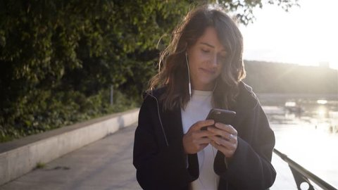 Relaxed young woman wearing a black hoodie listening to the music and walking along a river bank. Tracking real time establishing shot