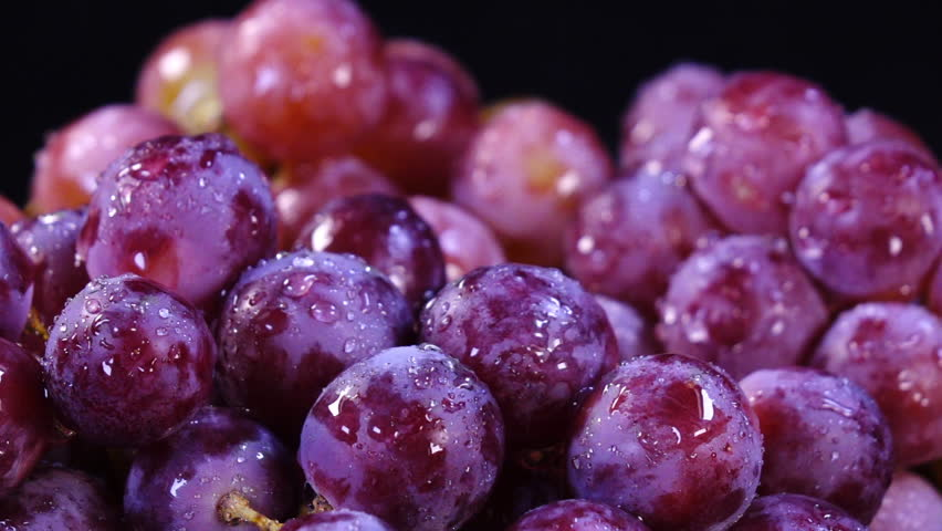 Amazing sprinkling in slow motion, 240fps, of pink and violet grapes close up, rotating to the right on black background. Eco product for healthy food. Excellent vegetarian macro with vibrant texture.