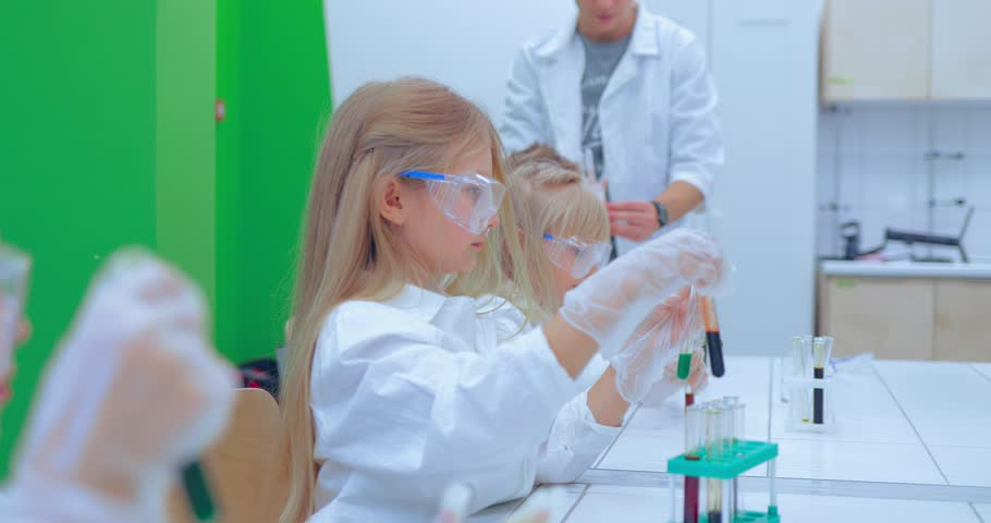 Teacher and students doing science experiment in school classroom. Children in chemistry class | Shutterstock HD Video #1007594164